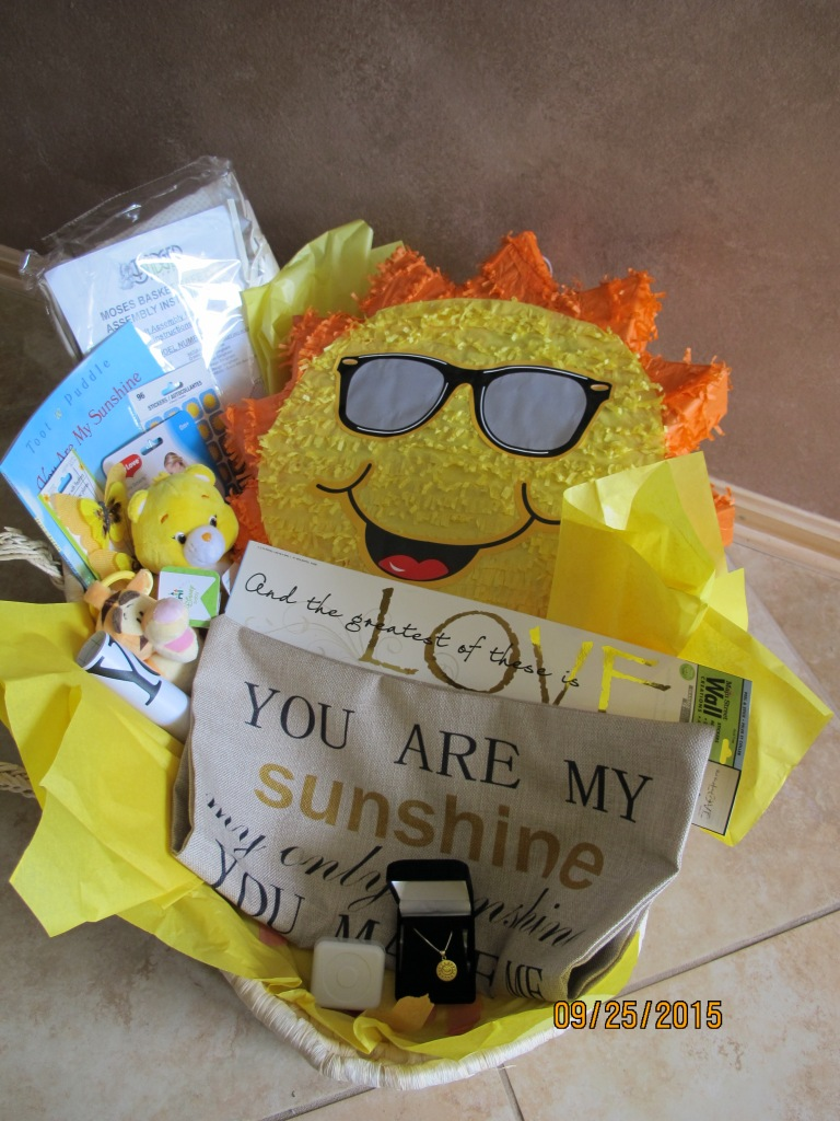 "RAFFLE #33 You Are My Sunshine Basket Thank you to Randi Muck for this beautiful donation in honor of Tina. • Badger Basket Company Natural Baby Moses Baby Basket with Bedding • My First ""Sunshine"" Rattle • Light Up Musical Tigger Toy that Plays ""You Are My Sunshine"" • Wind Up Music Box that Plays ""You Are My Sunshine"" • Sun Pinata • You Are My Sunshine Sterling Silver Necklace • You Are My Sunshine Custom Cotton Linen Cushion Pillow Cover • Just Play Care Bear Funshine Bean Plush • You Are My Sunshine Book • You Are My Sunshine Wall art • ""And The Greatest Of These is Love"" Wall Art Value: $135 *Raffle open to local participants only due to prize location."